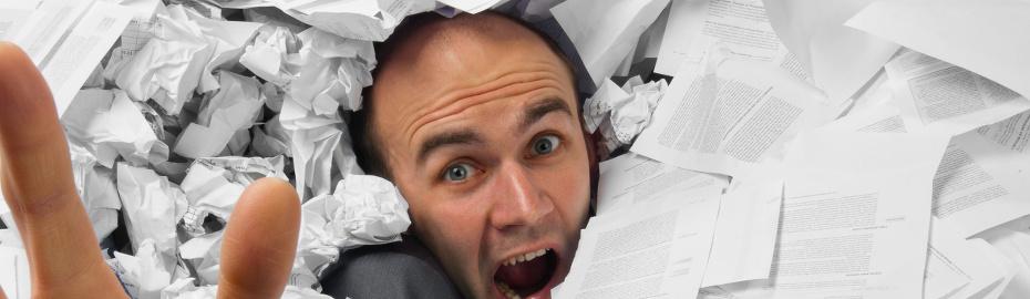 Mann versinkt in Papierunterlagen