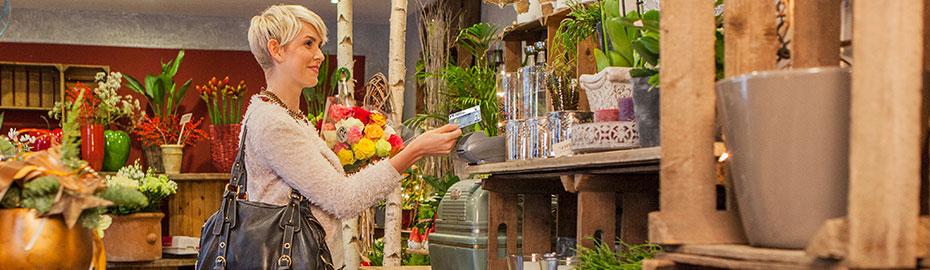 Frau im Blumenladen mit girocard in der Hand