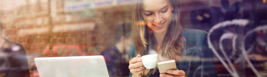 Frau mit Tasse und Smartphone in der Hand