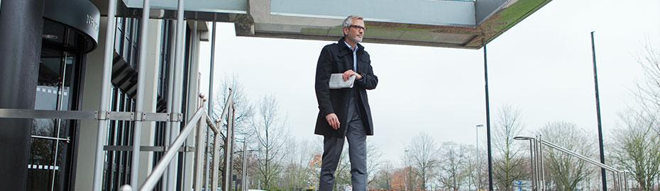 Älterer Mann mit Zeitung unter dem Arm