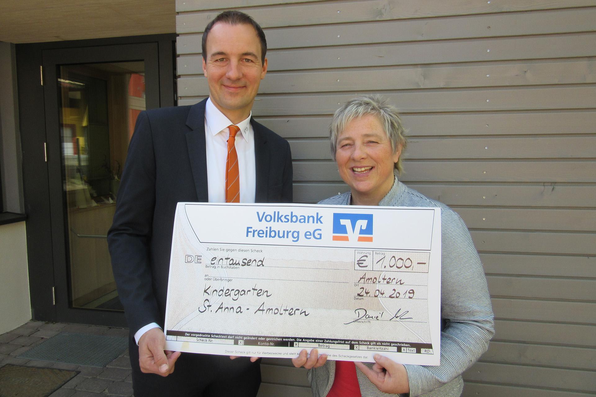 Regionalleiter der Volksbank Freiburg übergibt den Scheck an die Kindergartenleiterin Carmen Hofert