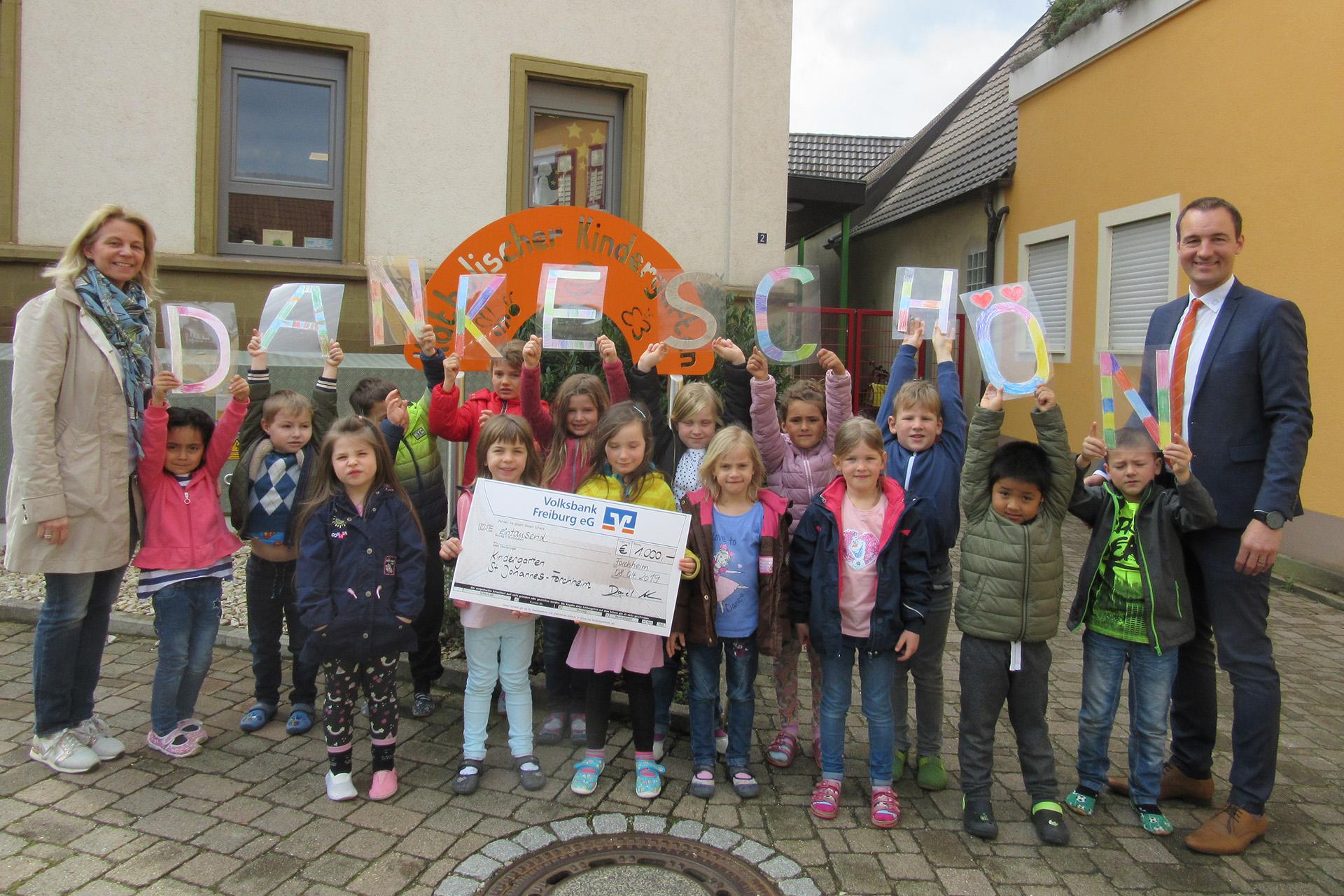 Daniel Mark, Regionalleiter der Volksbank Freiburg übergibt den Scheck an die Kindergartenleiterin Alexandra Nutto und die Schulanfänger des Kindergartens.