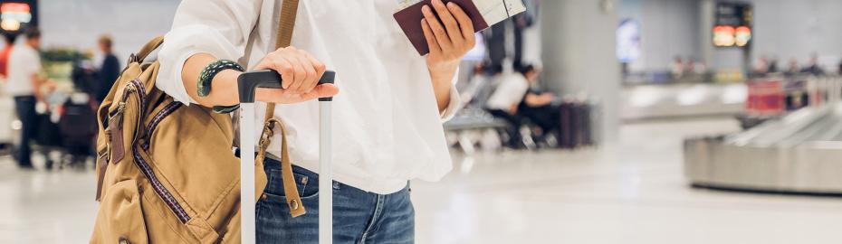 Frau mit Koffer und Rucksack am Flughafen