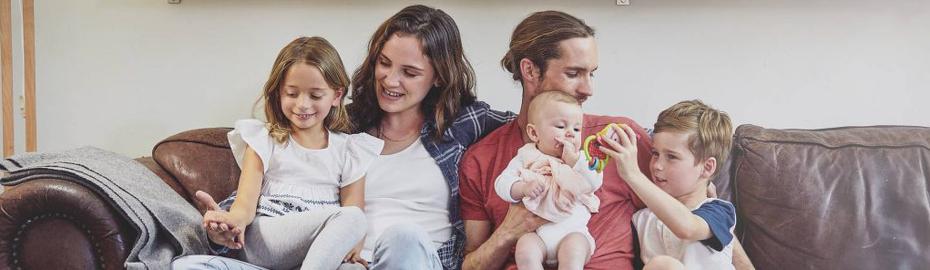 Mutter und Vater mit 3 Kindern auf Sofa