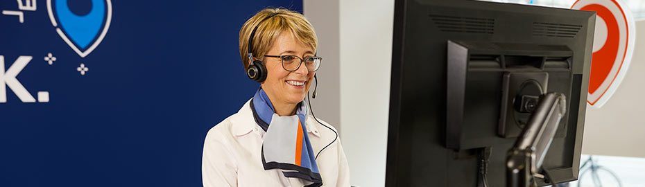 Frau sitzt mit Laptop auf dem Sofa