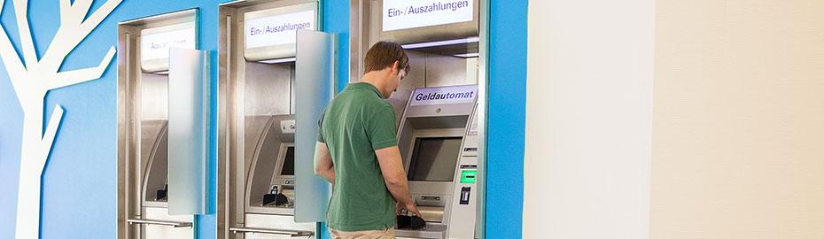 Junger Mann am Geldautomaten