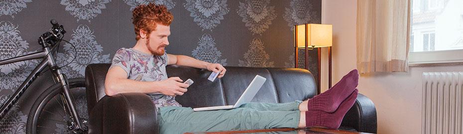 Junger Mann sitzt auf Sofa mit Laptop und Smartphone