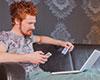 Junger Mann mit Laptop und Smartphone