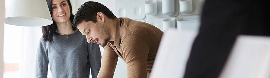 Junger Mann mit Smartphone am Tisch