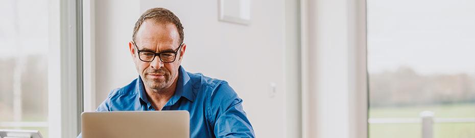 Junger Mann arbeitet am Computer.