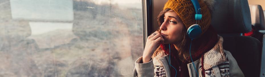 Junge Frau sitzt verträumt im Zug