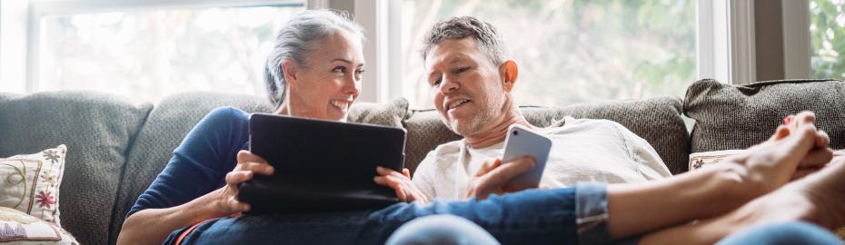 Älteres Paar mit Tablet und Smartphone